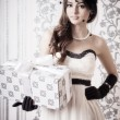 Beautiful vintage woman holding gift — Stock Photo