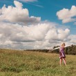 Little girl plays with balloon in grass — Stock Photo