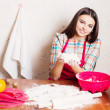 Beautiful girl cooking cake in kitchen — Stock Photo