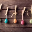 Easter eggs attach to rope with clothes pins on wooden backgroun — Stock Photo #41980531