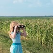 Girl looking through binoculars outdoor — Stock Photo