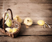 Goslings with easter eggs on wooden background — Stock Photo