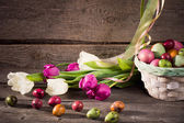 Tulips and easter eggs on wooden background — Stock Photo