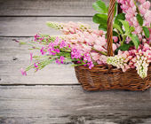 Flowers in basket on old background — Stock Photo