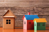 Houses from the paper on wooden background — Stock Photo