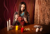 Young woman with runes and divination cards in room — Stock Photo