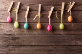 Easter eggs attach to rope with clothes pins on wooden backgroun — Foto Stock