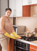 Mature woman doing the housework in the kitchen — Stock Photo