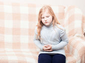 Child with stomach ache in sofa — ストック写真