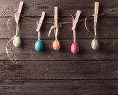 Easter eggs attach to rope with clothes pins on wooden backgroun — ストック写真
