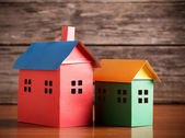 A paper houses stands over a wooden background. — Stock Photo