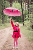Smiling little girl with umbrella — Stock fotografie