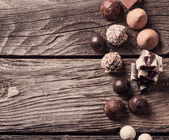 Chocolate on old wooden table — Stock Photo
