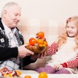 Grandfather with smile girl eating fruits at home — Stock Photo #44114735