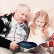 Grandfather and granddaughter sitting on the sofa and reading bo — Stock Photo #44114941