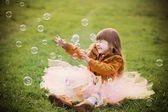 Little girl is playing with bubbles in a park — Stock Photo