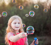 Girl blowing soap bubbles — Photo