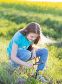 Girl with magnifying glass looks at flower — Stock Photo