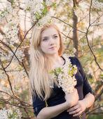 Attractive girl in blooming spring garden — Stock Photo