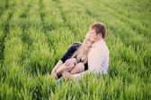 Young couple sitting on green grass — Stock Photo