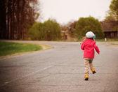Running little girl on road — Stock Photo