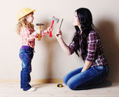 Mother with little girl plays in the builder — Stock Photo