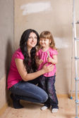 Happy Mother and child painting a wall with — Stockfoto
