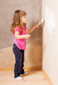 Little child with paintbrush on background old wall — Stockfoto