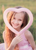Happy girl  holding a pink ball in the form of heart — Stock Photo
