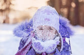 Cute little girl in warm hat and gloves blowing snow  — Stock Photo