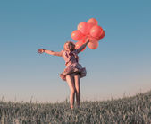 Girl with balloons jumping outdoor — Stock Photo