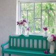 Green bench at window and flowers in vases — Stock Photo #48634071