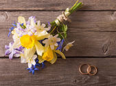 Wedding bouquet with rings on wooden background — Stock Photo