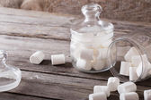 White marshmallows spilling from a jar on wooden background — Stock Photo