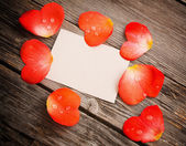 Red petal with paper on wooden background — Stock Photo