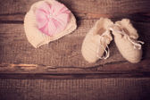 Baby's bootee and cap on wooden background — Stock Photo