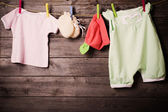 Children's clothing on a wooden background — Stock Photo