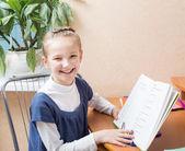 Jeune fille souriante, faire ses devoirs — Photo