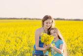 Happy women and girl in rape field — Stock Photo