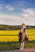 Happy women and girl in rape field — Stock Photo