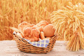 Bread and wheat on the wooden table in autumn field — Stock Photo