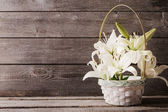 White lily in basket on wooden background — Stock Photo