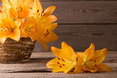Orange lily in basket on wooden background — Stock Photo