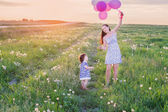 baby and mother with balloons outdoor — Stock Photo
