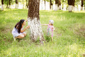 Mother and adorable baby daughter playing together hiding in sum — Stock Photo