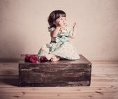 Little girl sits on an old suitcase — Foto Stock