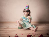 Little girl eating cake in a festive cap  in vintage style — Foto Stock
