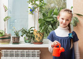 Happy girl watering potted plant at home — Stock Photo