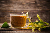 Cup of tea with linden on wooden background — Stock Photo