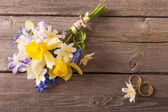 Wedding bouquet with rings on wooden background — Stockfoto